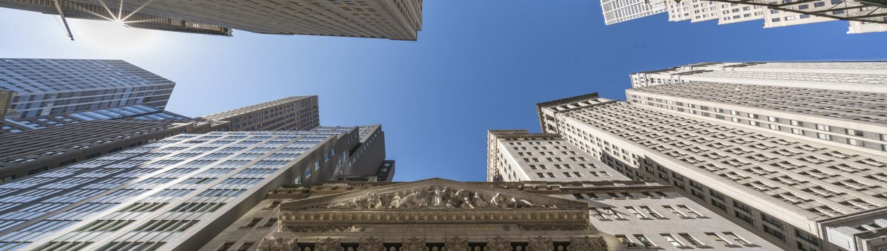 New York Stock Exchange and statue taken from down below with a clear blue sky_banner