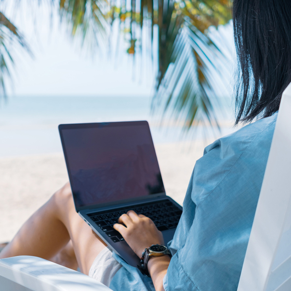 Woman using laptop and smartphone to work study at beach