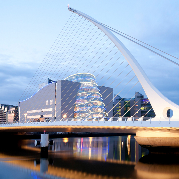 Samuel Beckett Bridge in Dublin after sunset. Modern bridge with modern buildings and skyscrapers in the backround.