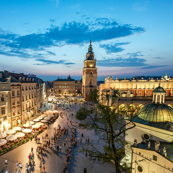 A view of the market square in Krakow at sunset with people walking around