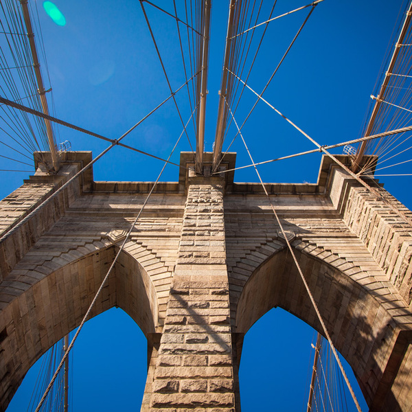 Upward View of the Brooklyn Bridge Against Bright Blue Sky