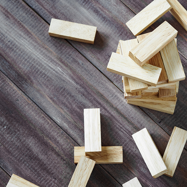 Scattered wooden jenga pieces on a wood background