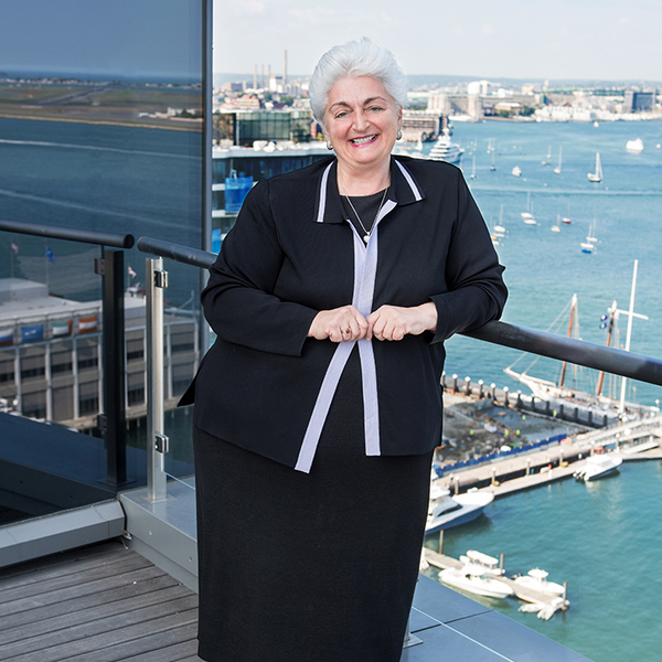 Regina M. Pisa leaning against a railing with a body of water behind her