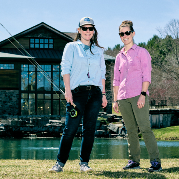 Jackie Kutzer and Christine Atkins in front of lake with fishing pole