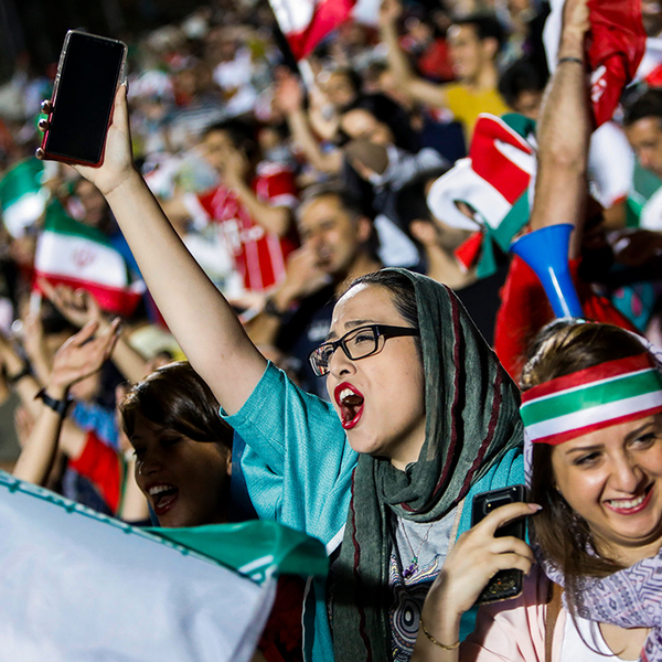 Iranian sports team supporters cheer in the stands at a game