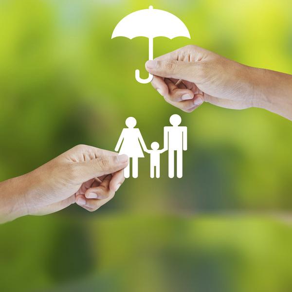 Hand holding a paper family and umbrella on green background