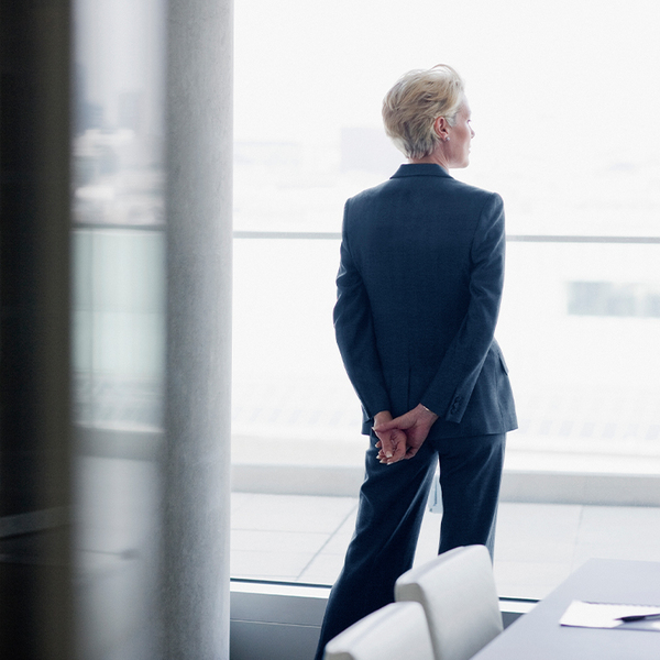 A business woman stands with her hands behind her back, looking outside a window
