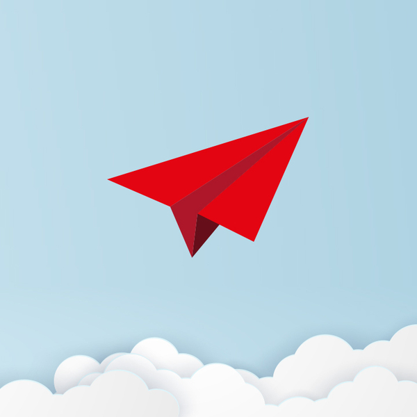Red Paper airplane in the sky above white fluffy clouds