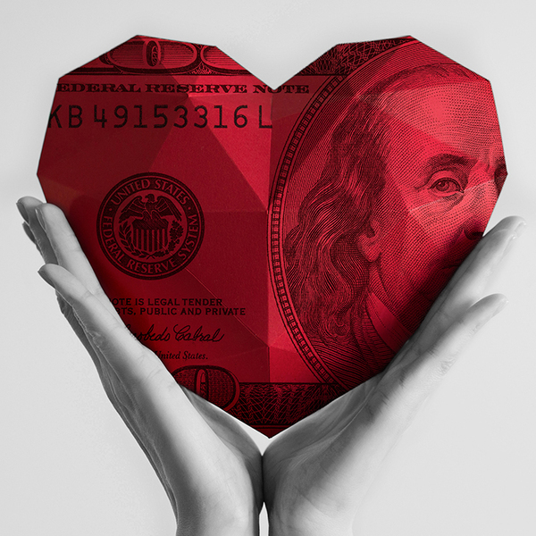 Giant red heart of money held by hands