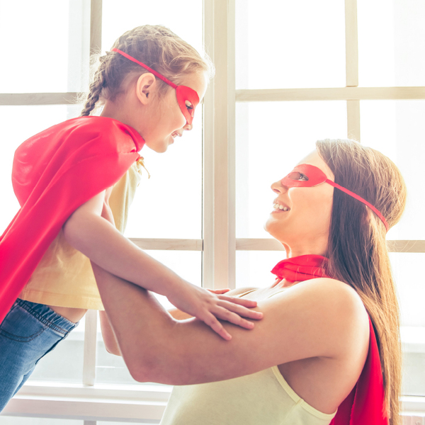 Mom holding up daughter as both wear superhero masks and capes