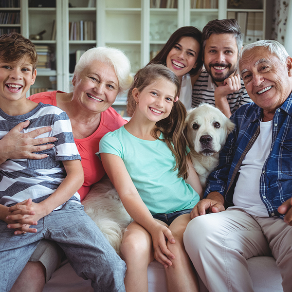 Multi-generation family and pet dog sit on a couch together smiling
