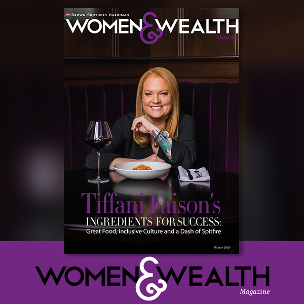 Tiffani Faison with a plate of food and a glass of wine in front of her