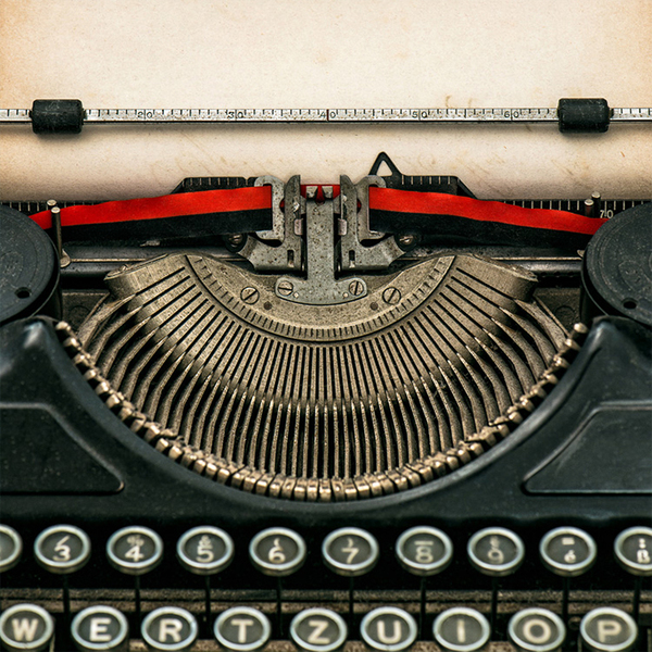 an old-fashioned typewriter with blank paper in it