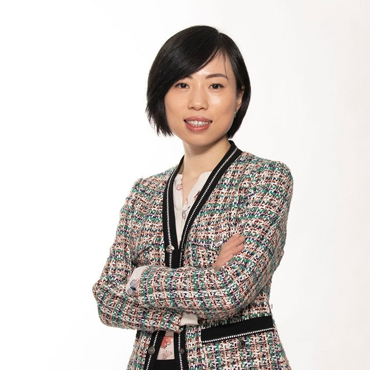 Smiling business woman with short black hair wearing a black, green and pink tweed blazer with arms crossed over her chest on a white backdrop