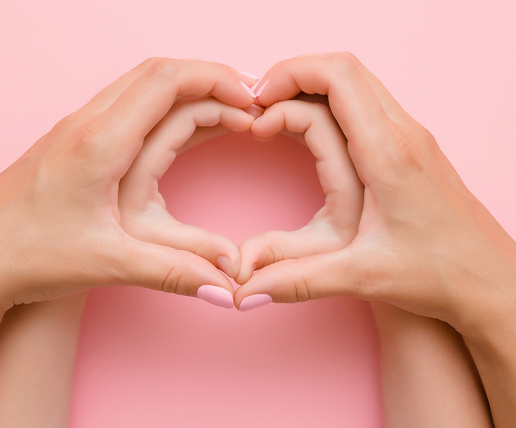 Adult hands forming a heart around a child's hand forming a heart on a pink background