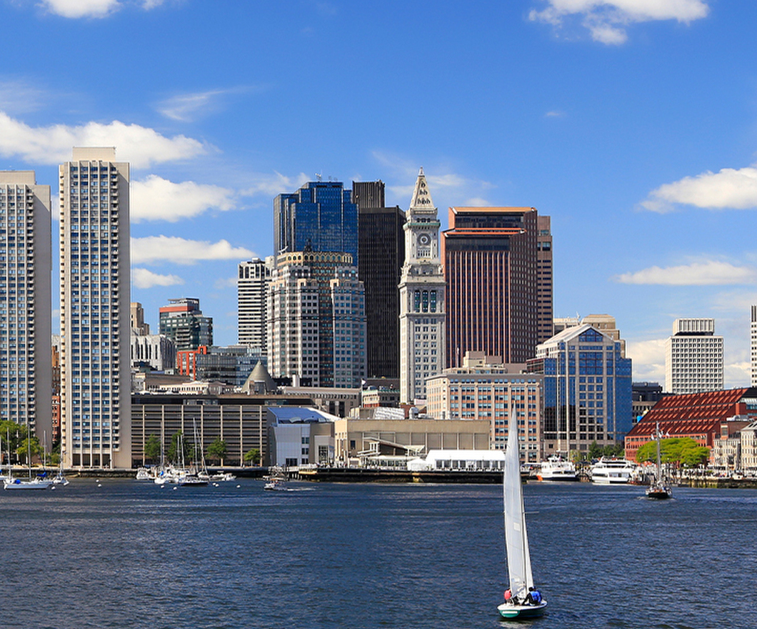 Boston city skyline seen behind a body of water with a sailboat in the center of the image