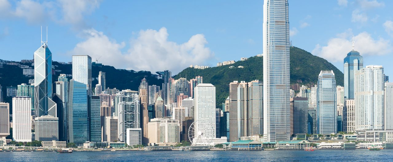 Hong Kong view from Victoria Harbour on sunny day with green mountains in the background