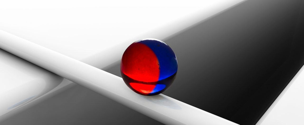 Blue red marble balancing on white cylinder