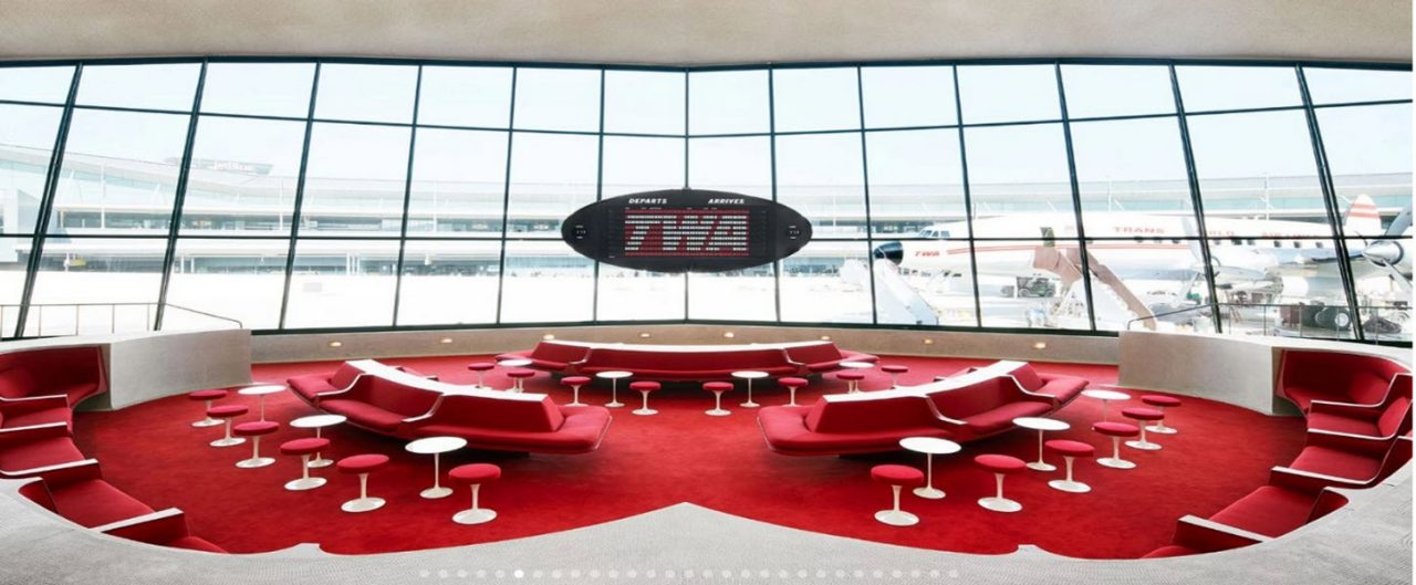 TWA conference room with a red carpet and red upholstered couches and chairs with a big window overlooking an airport