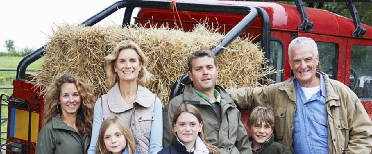 Family of seven in front of a truck and hay bail