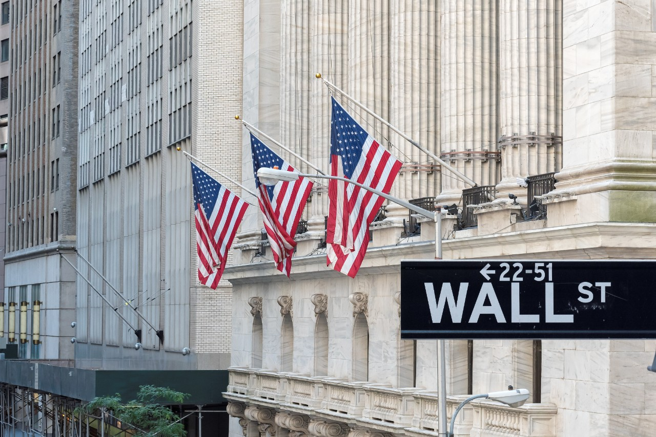 Wall Street sign with American flags and New York Stock Exchange in New York City