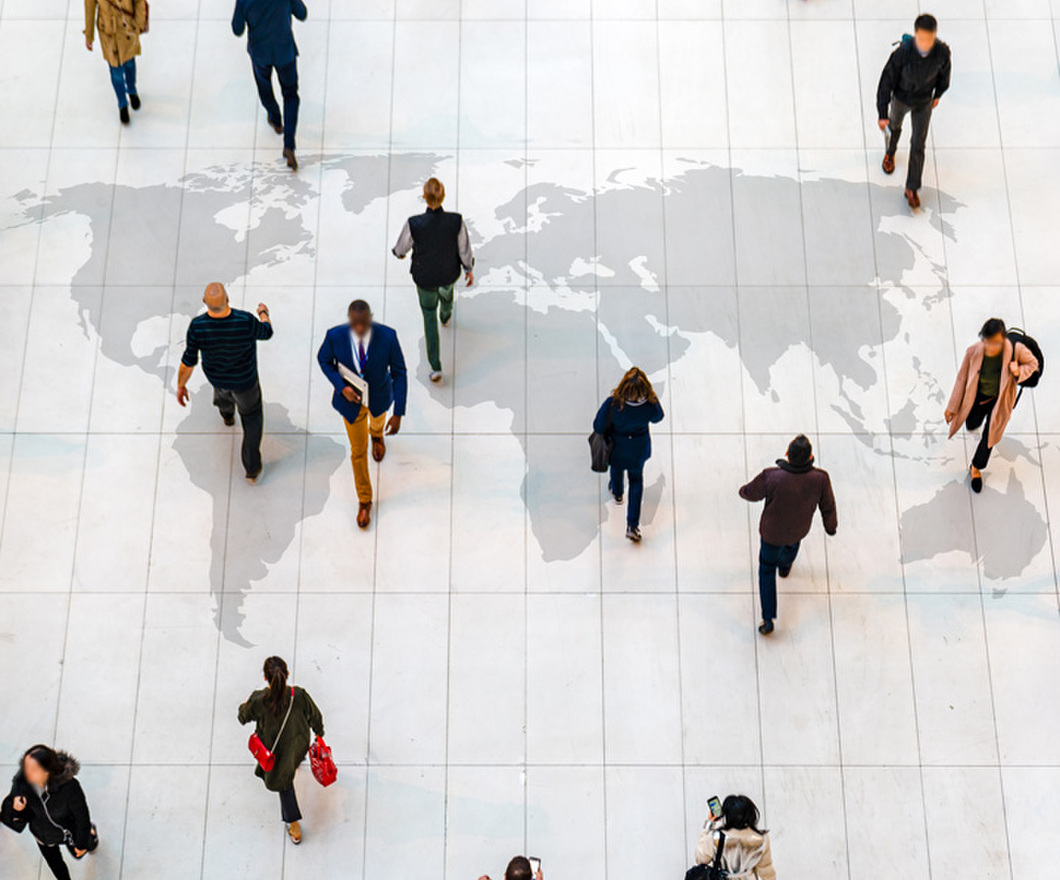 Top view of people walking on white floor with world map.